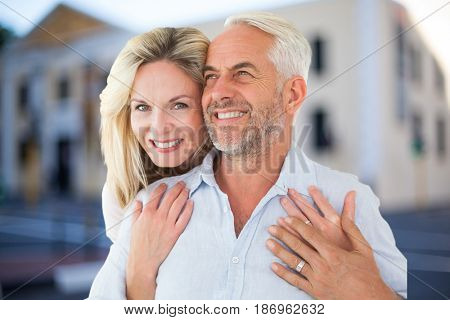 Digital composite of Happy woman embracing man against house