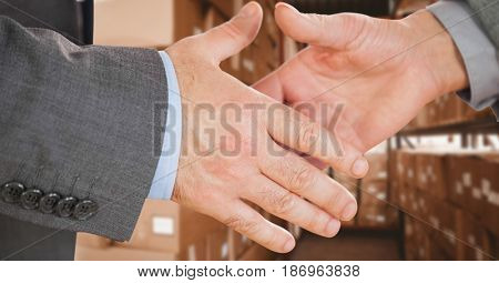 Digital composite of Business executives shaking hands in warehouse