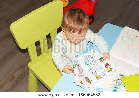 A little girl's baby paints pictures in a children's book at a table. Game room for small children, learning and developing kids, books and pencils