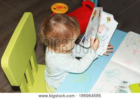 A small child looks at the pictures in the children's book at the children's table. A girl is reading a children's book in the children's room.