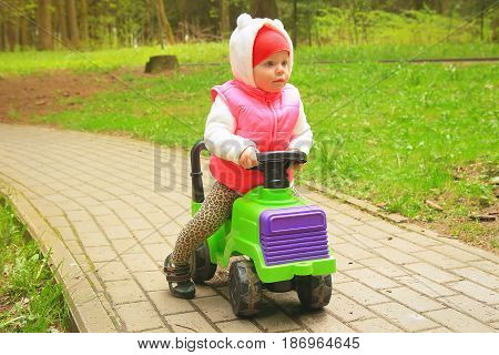 A little girl is riding on a toy car in a green park on a sunny day. Playing children outdoors, relaxing, chatting with children. Ride a toy car.