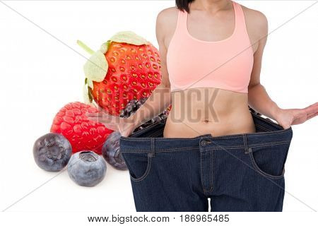 Digital composite of Midsection of woman in loose jeans by fruits representing weight loss concept