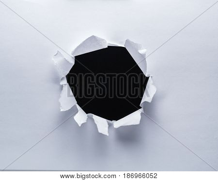 Hole on a paper. Black background in the hole.