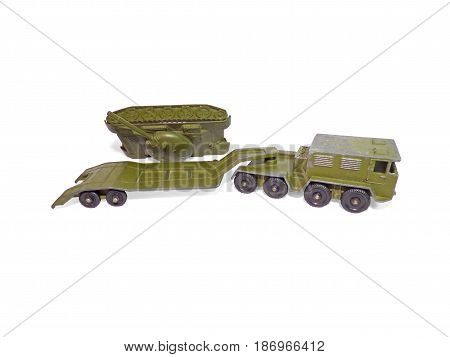Military cargo vehicle on white background with fallen tank. Old soviet childrens toys.