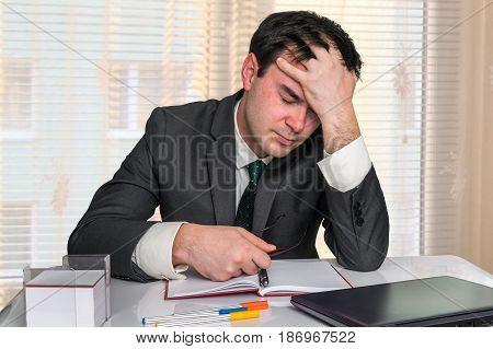 Depressed Businessman With Headache In The Office
