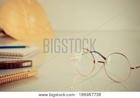 Construction worker tools with eyeglasses on the table