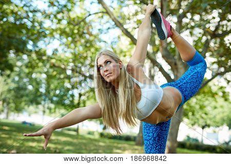 Young blonde woman doing yoga balancing exercises at citypark.
