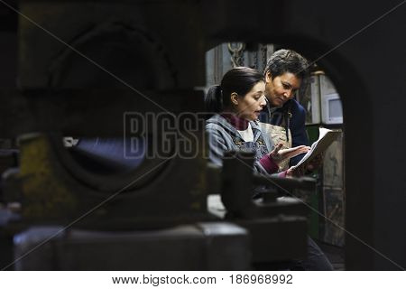 Workers looking at paperwork in factory