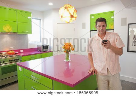 Hispanic man text messaging on cell phone in kitchen