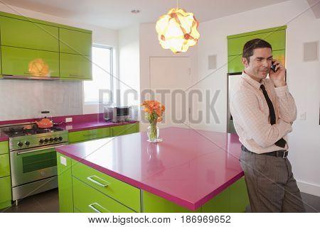 Hispanic businessman talking on cell phone in kitchen
