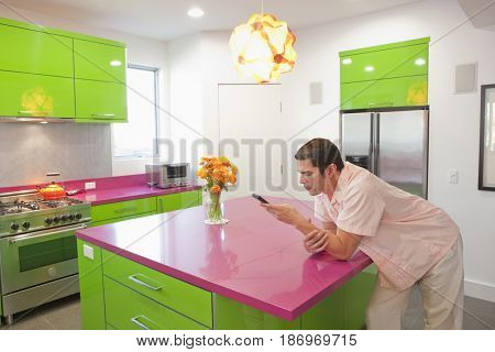 Hispanic man leaning on counter text messaging on cell phone