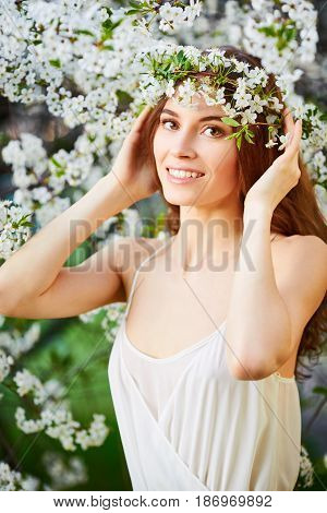 Young Beautiful Woman In White Dress In Circlet Of Flowers