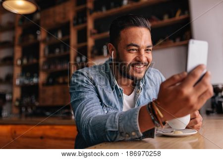 Handsome young man sitting at cafe making video call from his mobile phone. Caucasian male at coffee shop having a videochat on smart phone.