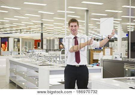 Caucasian salesman standing in home supply store holding blank card