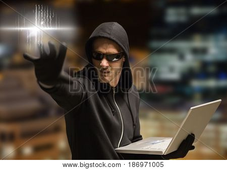 Digital composite of Criminal in hood on laptop in front of night city
