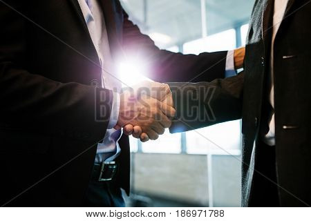 Close up of business people shaking hands in office. Business men shaking hands with each other.