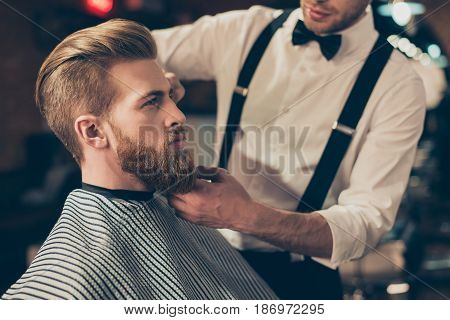Cropped Photo Of A Classy Dressed Barber Shop Stylist Working For A Perfect Look Of A Red Bearded Gu