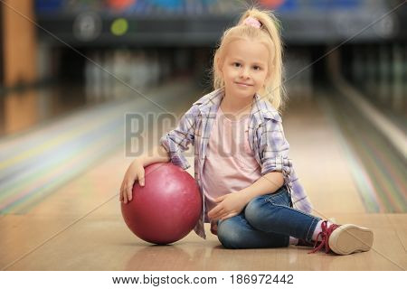 Cute little girl with ball sitting on floor in bowling club
