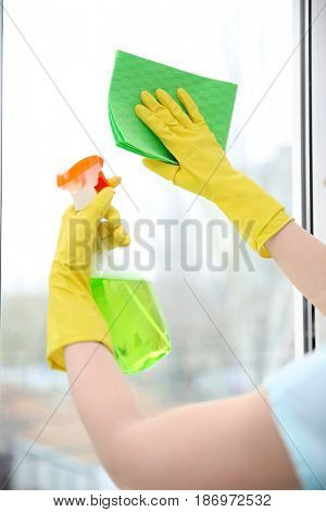 Hands of young woman cleaning window