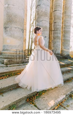 The side view of the bride in the long pompous dress standing on the stairs of the ancient building