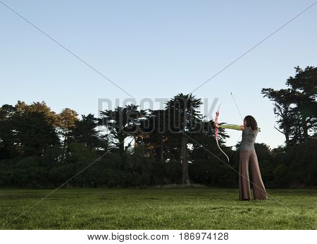 Black archer aiming bow and arrow in field