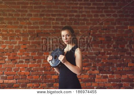 Woman in sportswear doing workout on brick background.