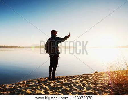 Man Takes Photo Of  Evening Sea. Hiker With Backpack With Phone In Hand Along Beach