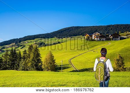 Active elderly woman-tourist with backpack admiring the beauty of the Dolomites. Northern Italy, Tirol. The concept of an active and eco-tourism