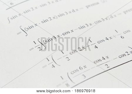 Closeup of a page of math book with integrals and trigonometric functions
