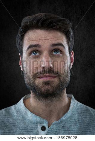Digital composite of Man looking up against black wall