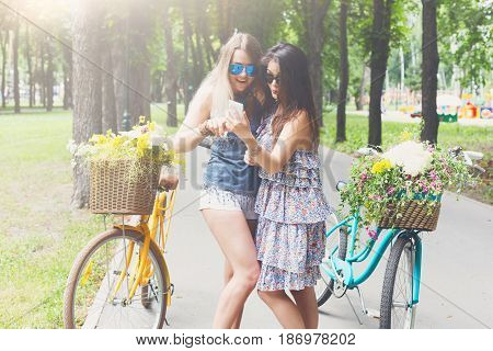 Young girls surf mobile internet at park ride. Beautiful women with bicycles with baskets full of wild flowers.