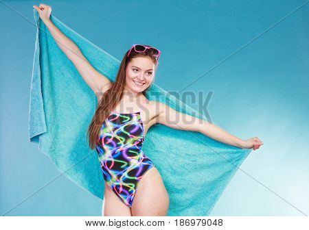 Happy smiling young woman girl in swimsuit swimwear with towel and sunglasses on blue. Summer holiday vacation relax.