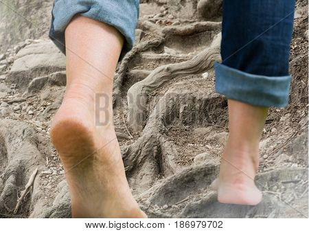 Digital composite of Bare feet walking climbing rough tree roots terrain hill