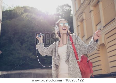 Carefree Girl Is Listening To Favourite Song And Dancing Outside, Wearing Cozy Outfit And Sunglasses