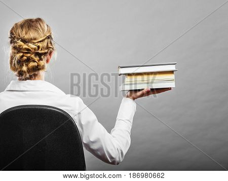 Education school or business concept. Woman female student sitting on chair holding stack books. Back view grunge background