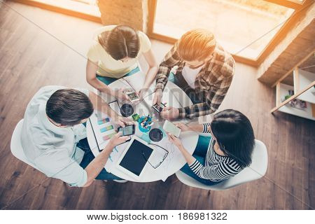 Top-view Of Four Students Sitting By The Table Using Their Smartphones For Searching For Information