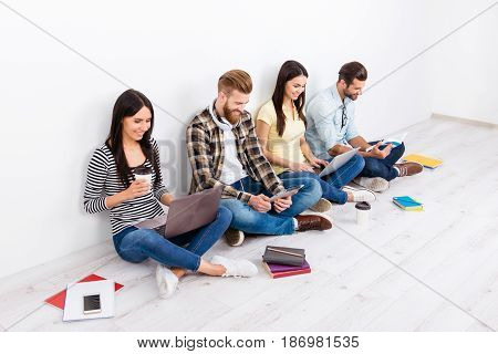 Company Of Happy Students Sitting On The Floor With Crossed Legs Studying And Smiling. They Are Prep