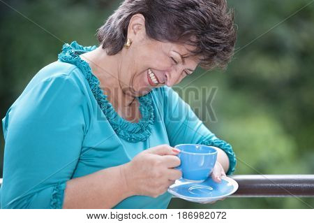 Laughing Hispanic woman drinking coffee