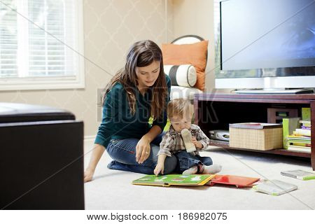 Caucasian mother reading book to son