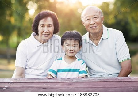 Chinese grandparents sitting outdoors with grandson