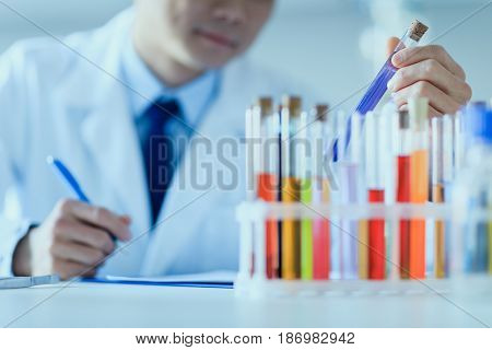 Cropped Shot Of Scientist In Lab Coat Holding Test Tube And Taking Notes, Laboratory Researcher Conc