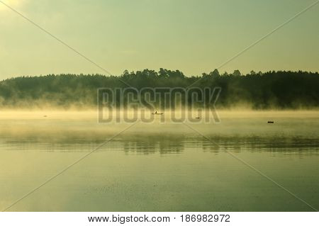 Front of a small boat with the sky reflected in a river in the Amazon rain forest in Peru