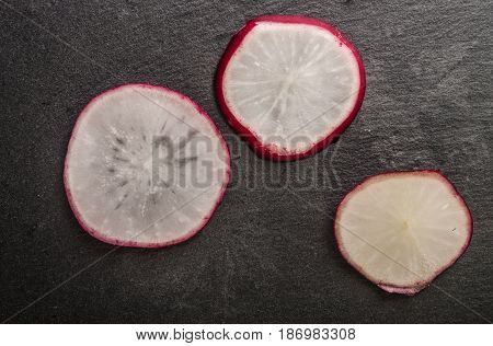 fresh radish cut in black background close up