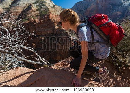 Young lady hiker with backpack carefully looks down from high cliff