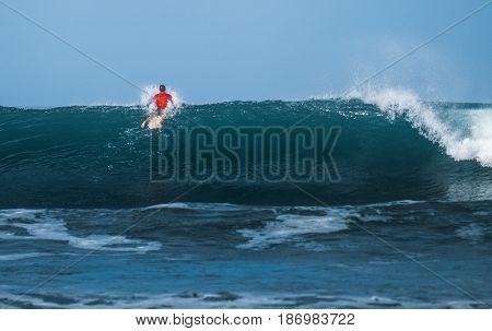 Surfer passing big ocean wave