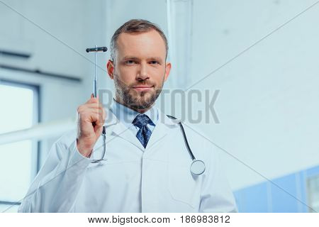 portrait of confident doctor with stethoscope holding reflex hammer