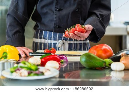 Chef cutting tomatoes for salad in hotel kitchen