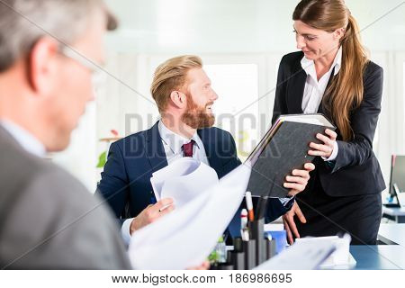 Assistant brings ring binder to meeting of managers