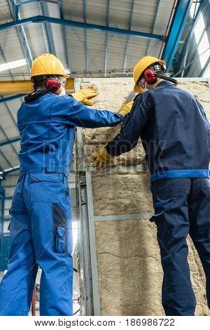 Two Asian workers applying insulation material to an industrial steam boiler
