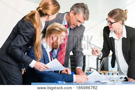 Manager is checking documents brought by two assistants